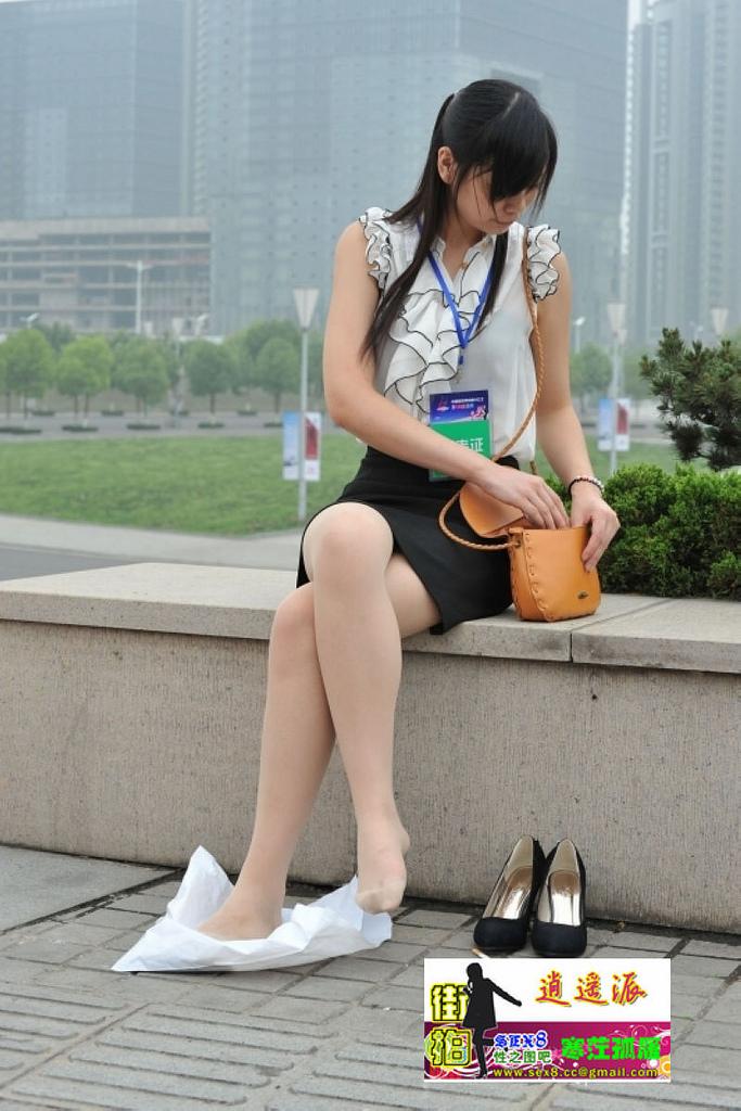 穿肉丝的美女记者累了在石凳上休息