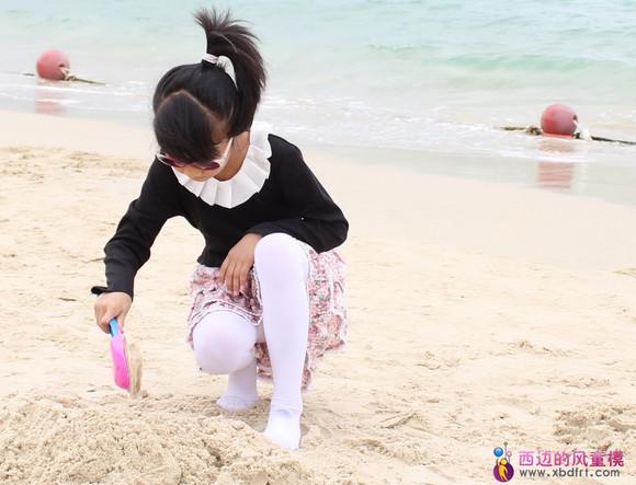 小女孩穿着白裤袜在沙滩上玩