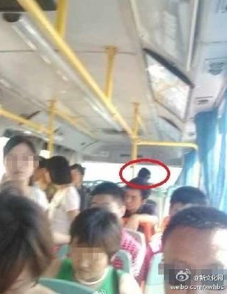 公交前排的中年女子摸着肚子