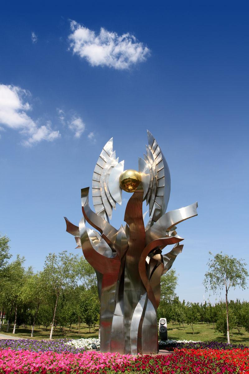 雕塑,白刚雕塑,不锈钢雕塑,正能量雕塑,蓝天,白云,鲜花图片