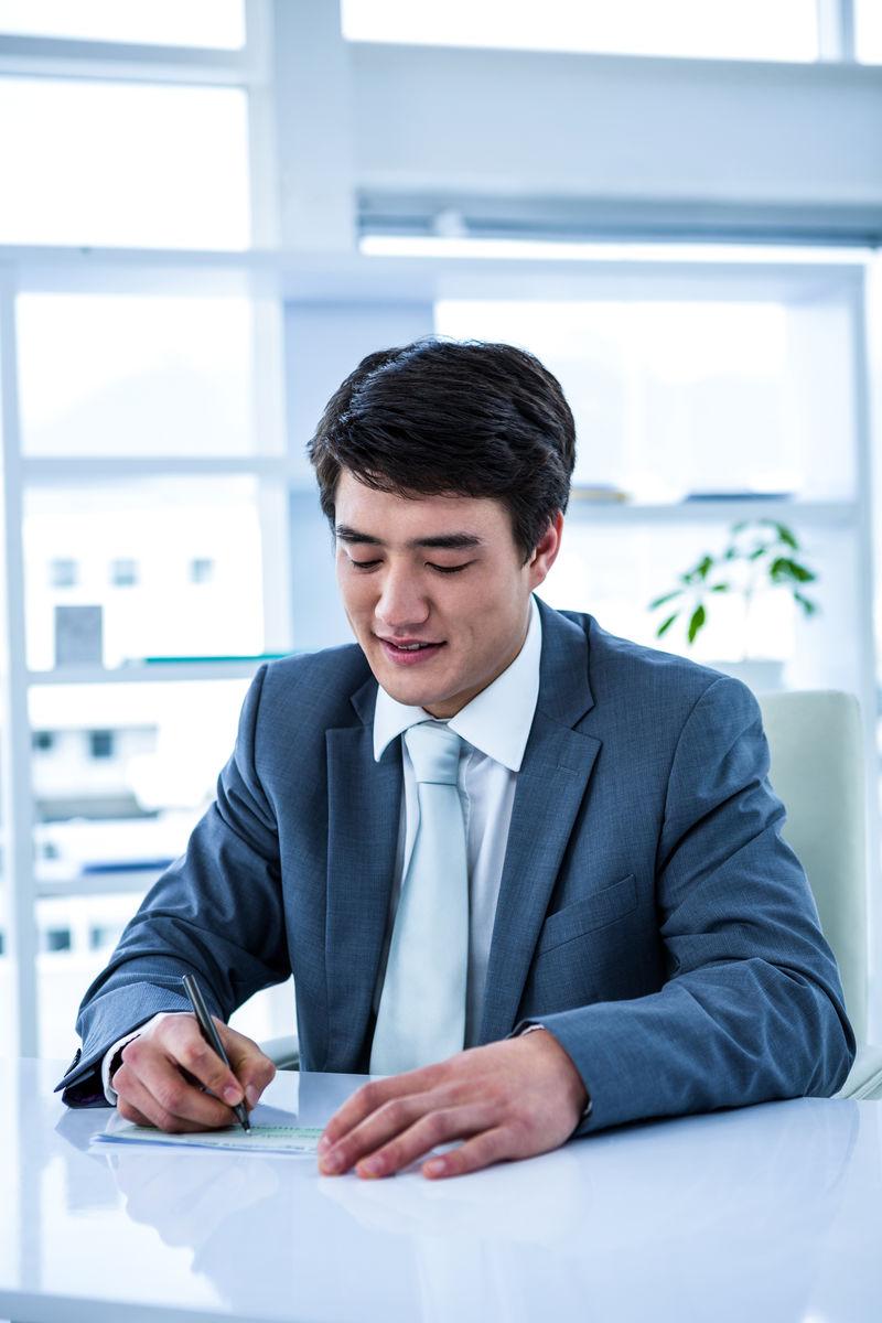 张�9�n[�n�KNY _微笑的亚洲商人在他的办公室里开了一张支票