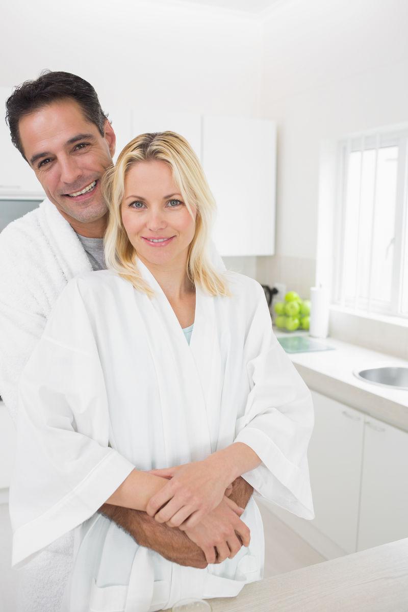 一个男人拥抱女人的肖像从厨房的后面在家里图片