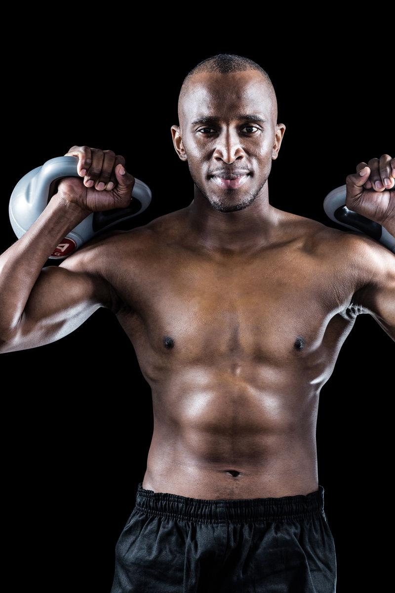 肌肉_自信的人的肌肉在黑色的背景上壶铃运动画像