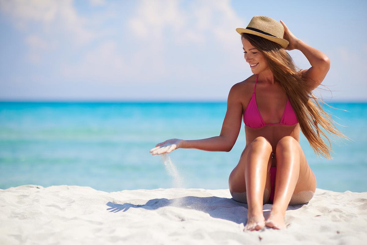 坐的_美丽性感女子坐在沙滩上的海上背景