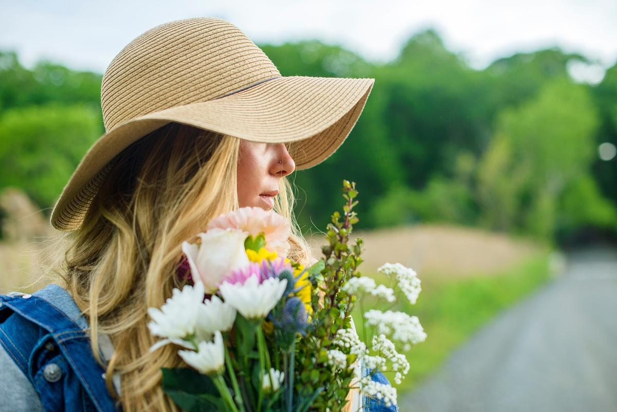 年轻妇女的画像与一束鲜花和戴草帽图片