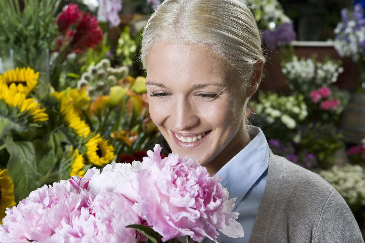 一个女人看着一束鲜花微笑图片