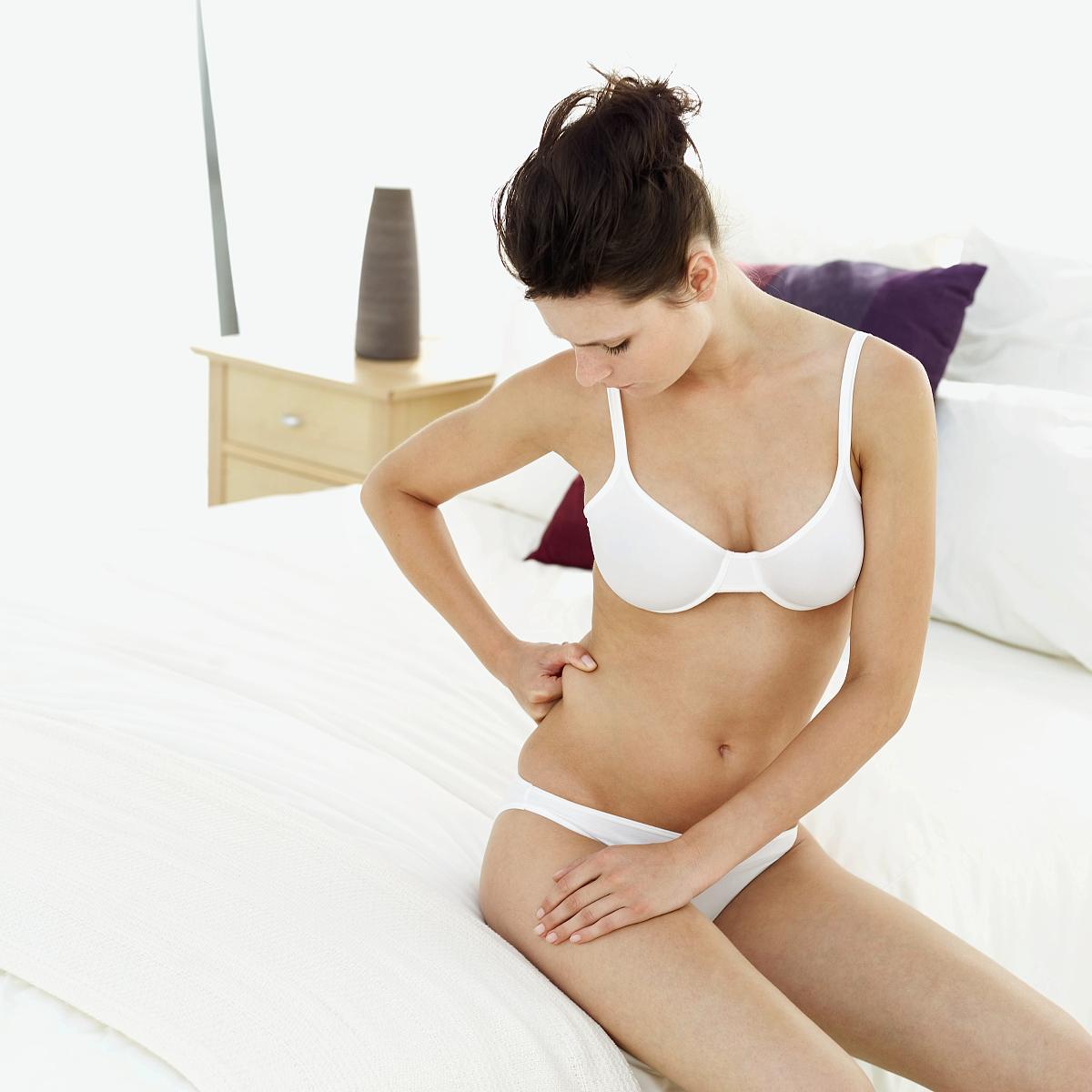 坐的_一个穿着内衣的年轻女子坐在床上,检查腰部的脂肪