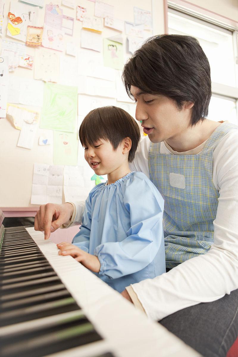 幼儿园老师和男孩在弹钢琴图片