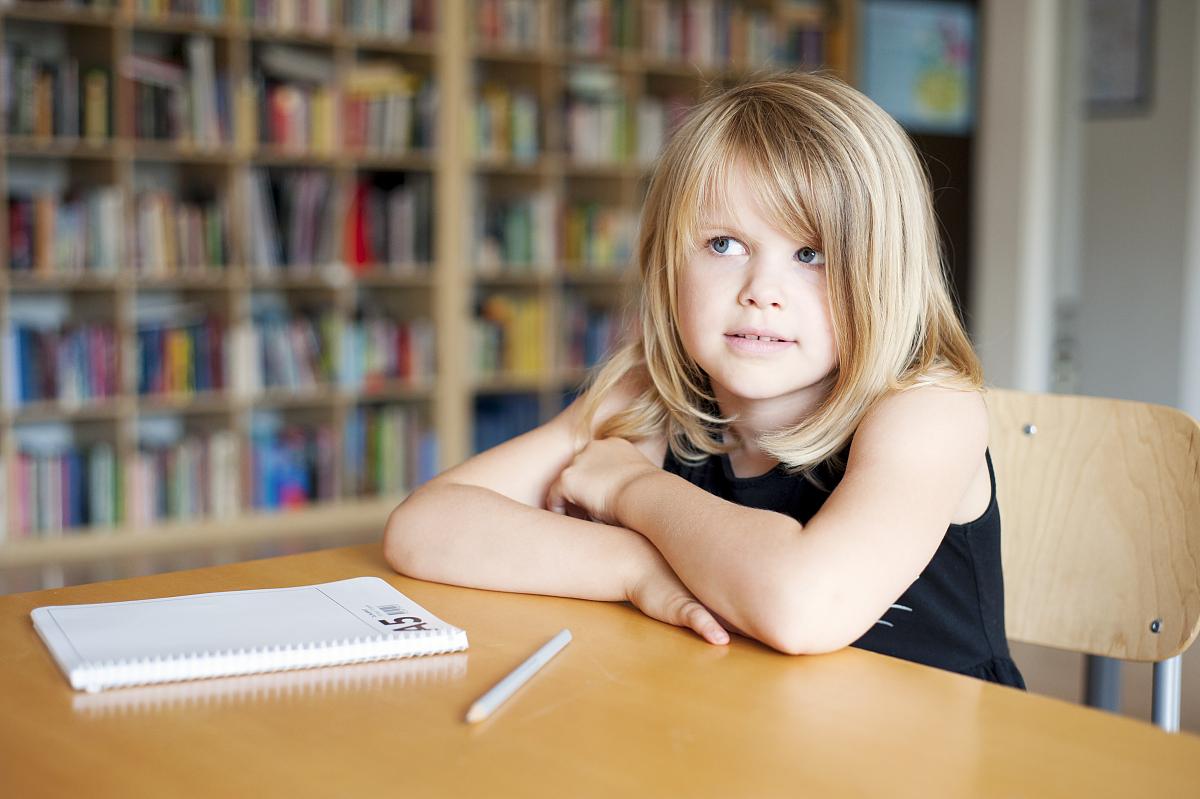 坐的_体贴的女孩坐在教室的书桌旁
