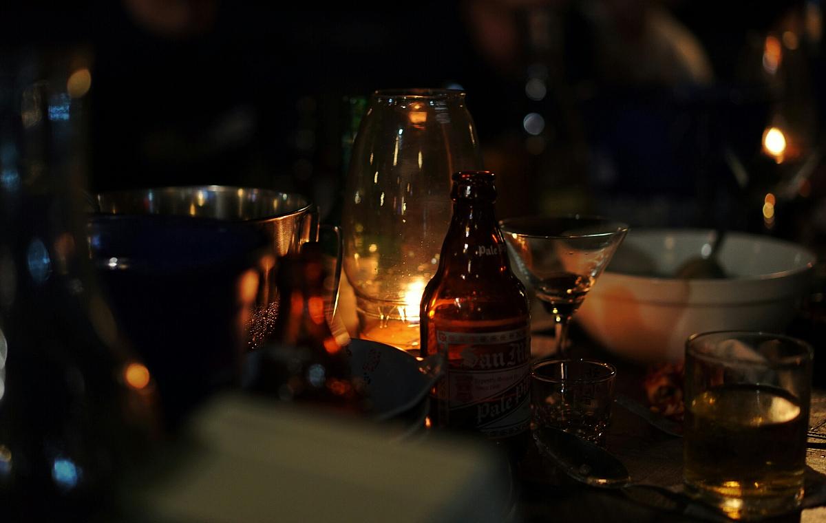 点燃的烛光与啤酒瓶和饮用玻璃在桌子上图片