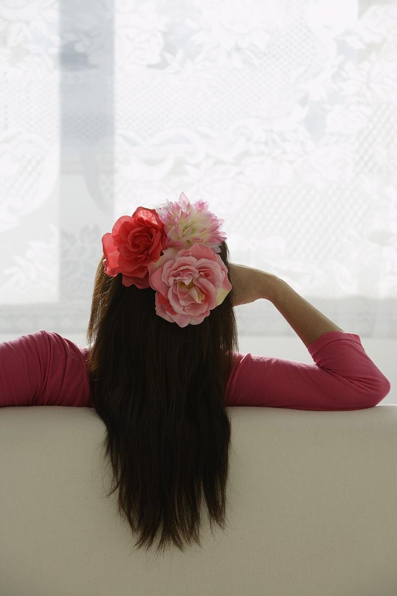 女人用鲜花在头发上望向窗外.图片