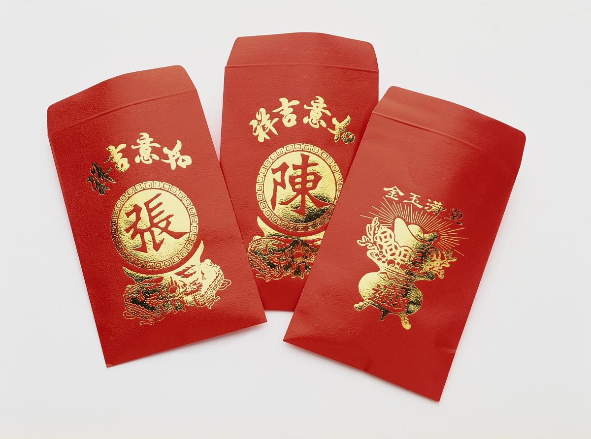 红色吉祥钱包用黄金插图和汉字装饰,给孩子在农历新年早上,特写.图片