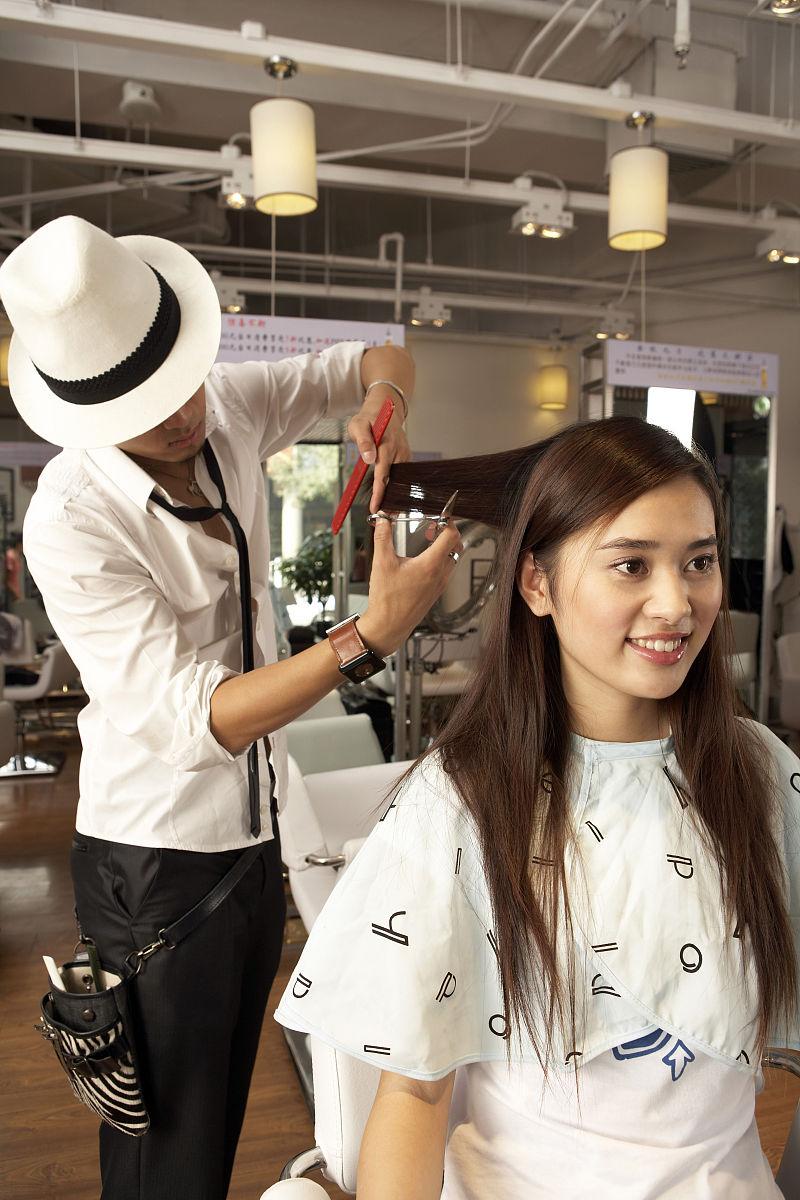 理发师给年轻女顾客剪头发图片