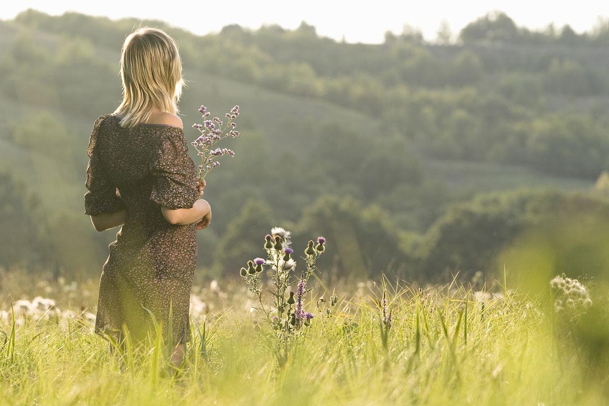 俄罗斯voronezskaya领土,与鲜花站在草地上的年轻女子后视图图片