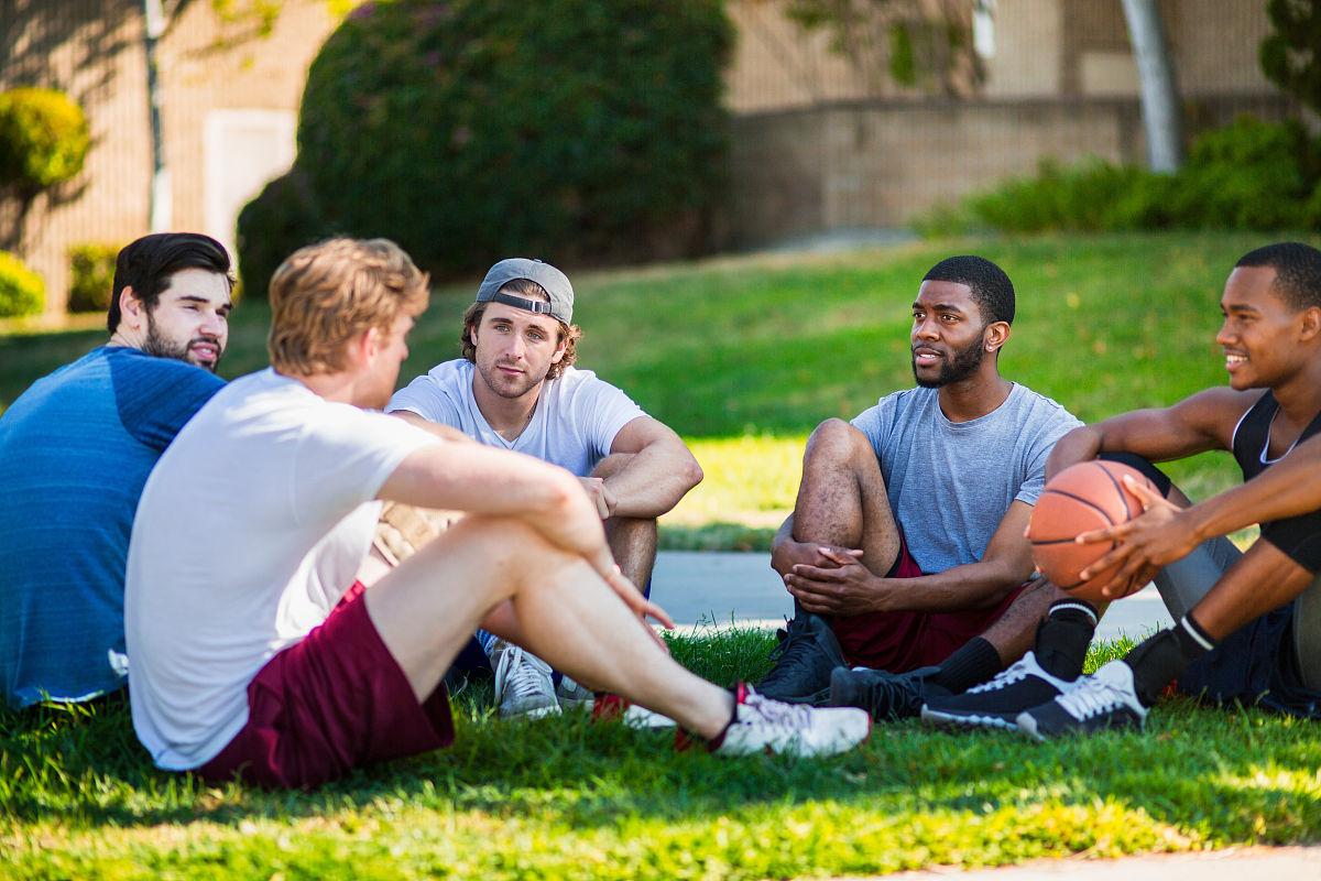 坐的_一群男朋友一起坐在公园里,笑着