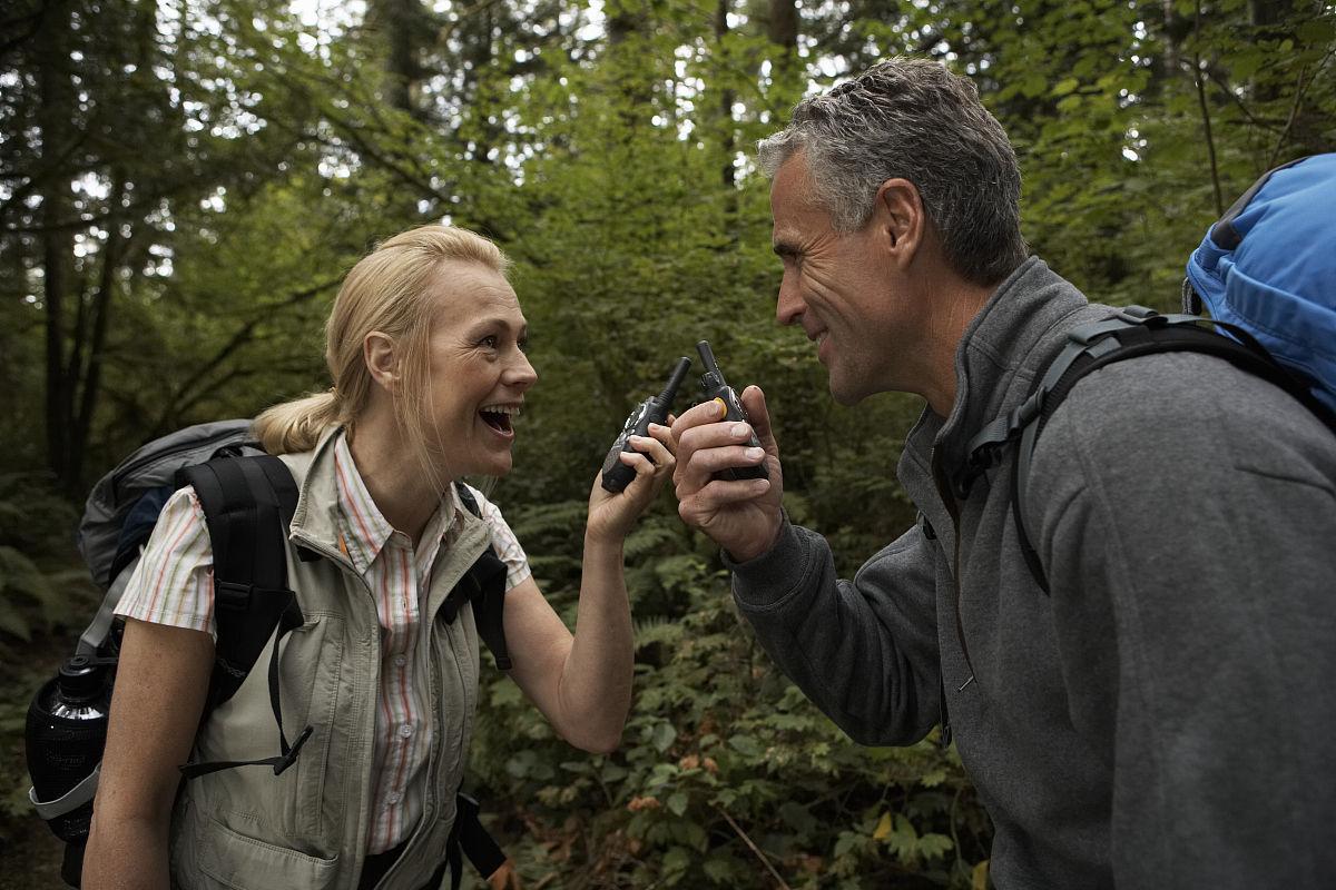 成熟的男人和女人对着对讲机在森林,微笑图片