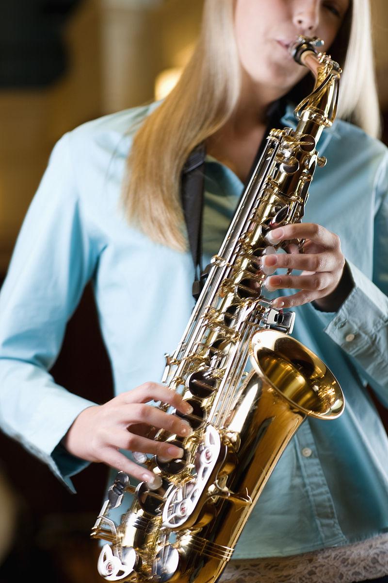 演奏萨克斯管的年轻女子图片