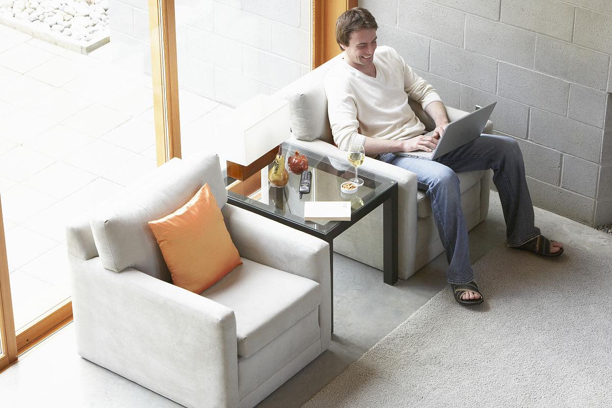 坐的_男子坐在扶手椅上,使用笔记本电脑和笑,高架视图