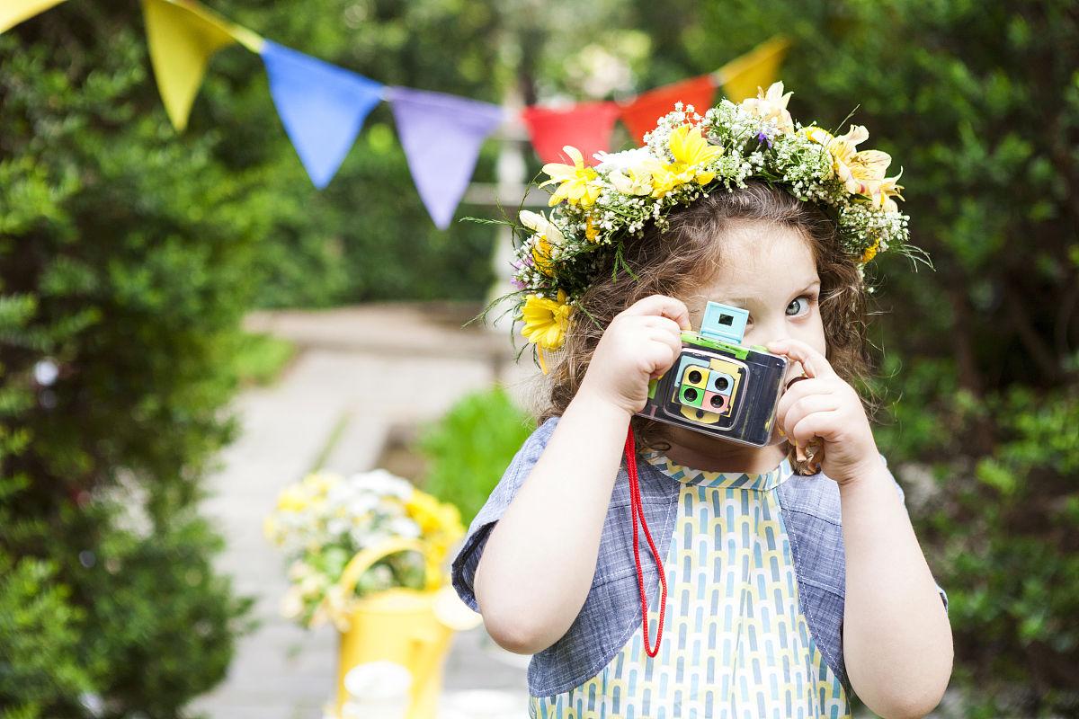 小女孩穿着鲜花拍照与老式相机图片