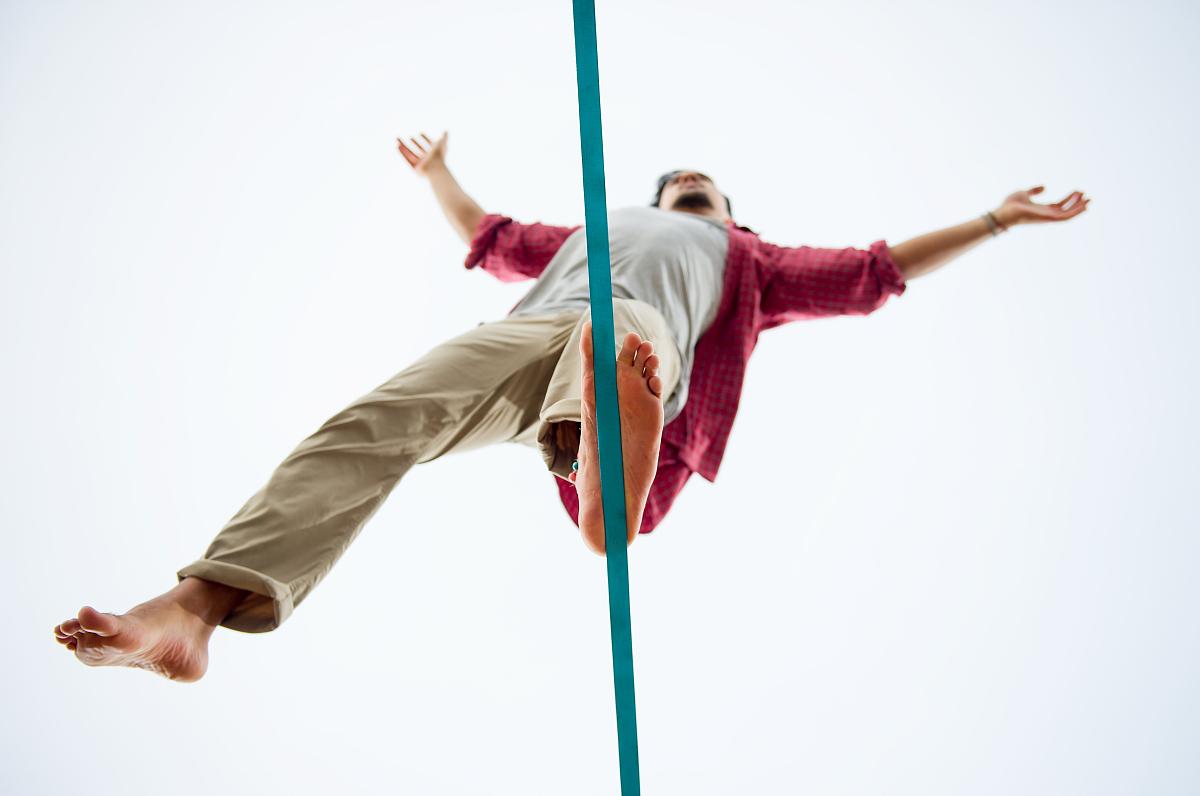 平衡_年轻人用一只脚在绳的平衡