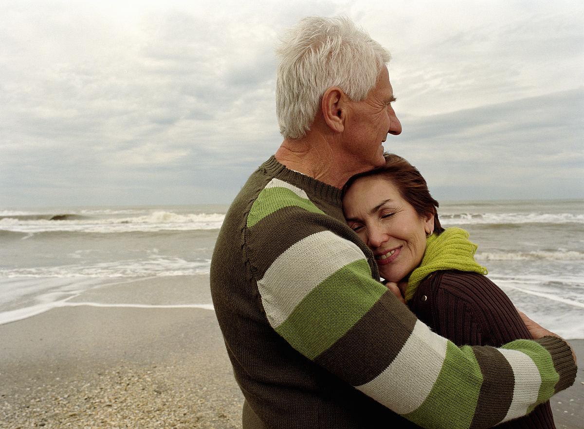 在海滩上拥抱的男男女女,微笑,侧面图片