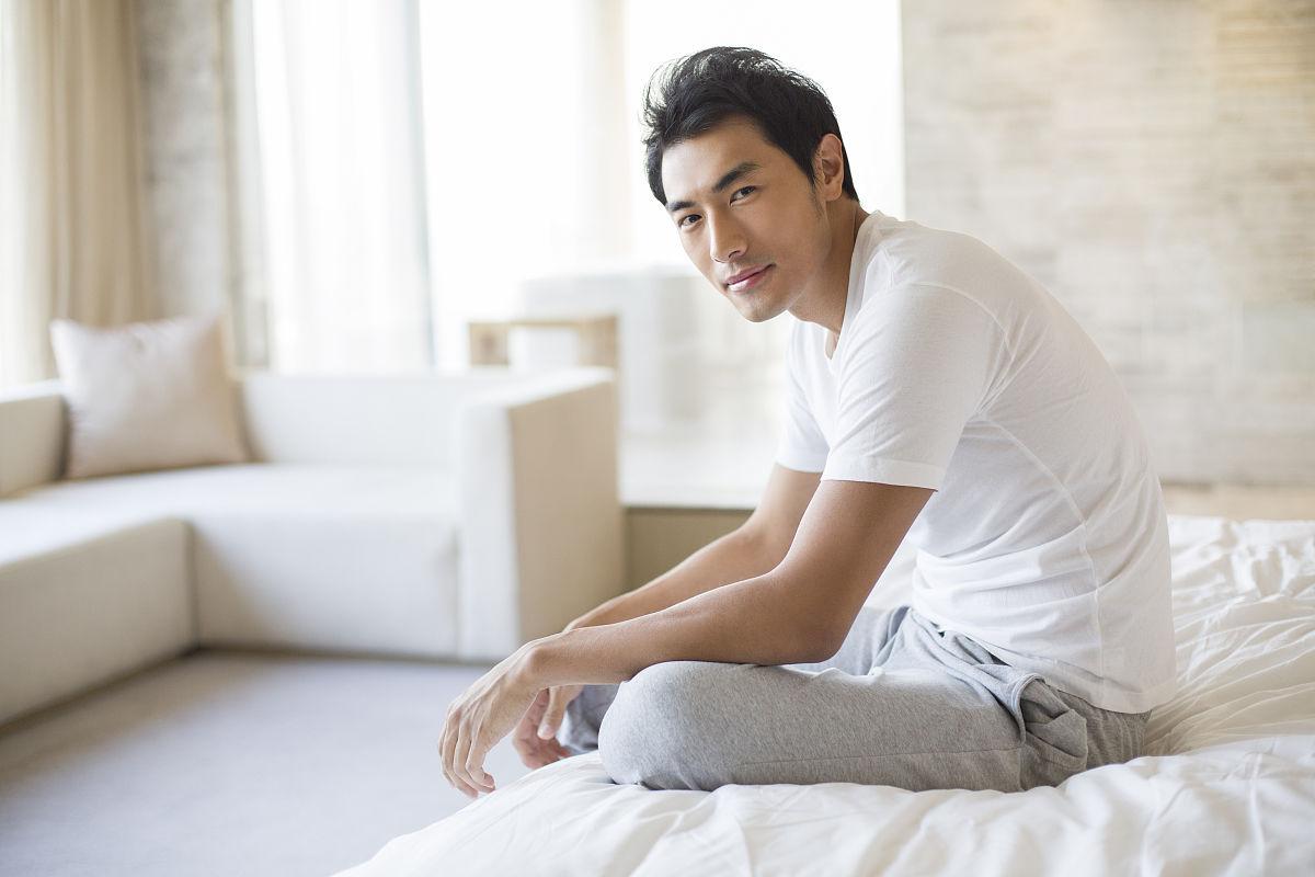 坐的_年轻男子坐在床上