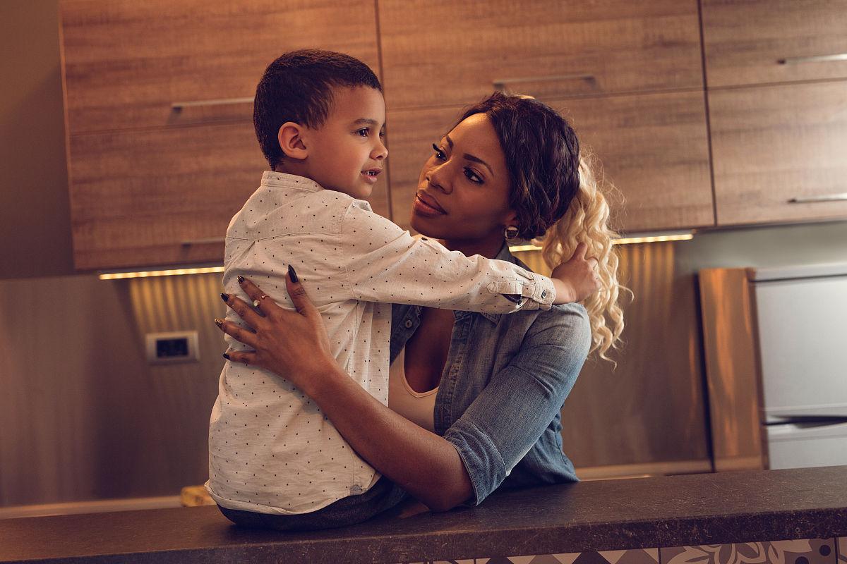 非裔美国人母子在厨房拥抱.图片
