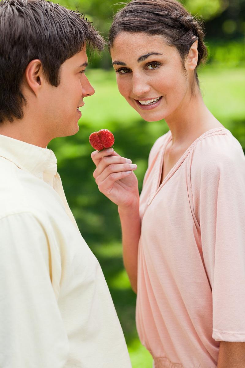 �n=獻_在公园里,一位妇女一边向朋友一边献草莓