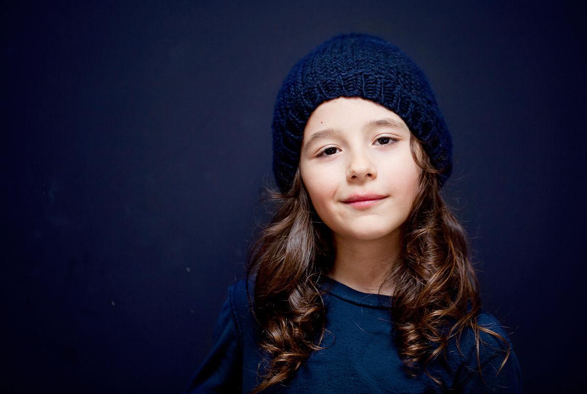 可爱的微笑男孩长头发和帽子反对蓝色背景图片