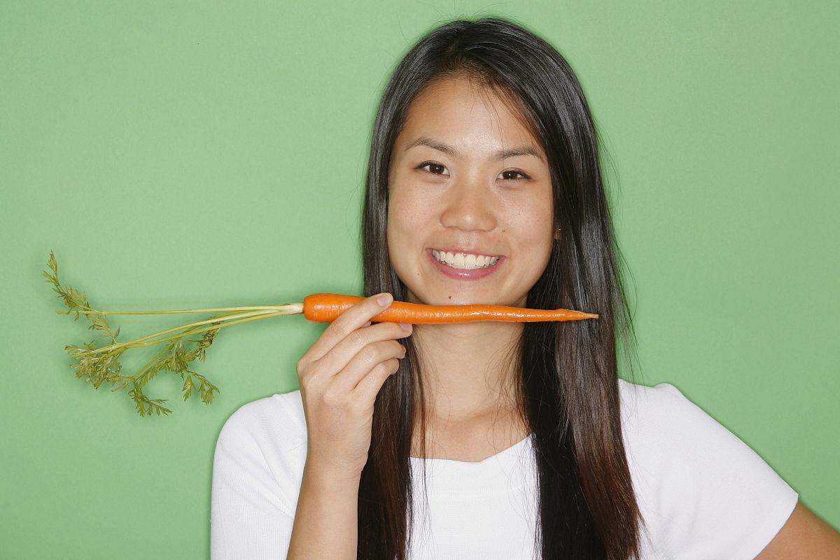 胡囹f�X��yK�x�~XZ���_抱着胡萝卜的年轻女子,摄影棚,肖像
