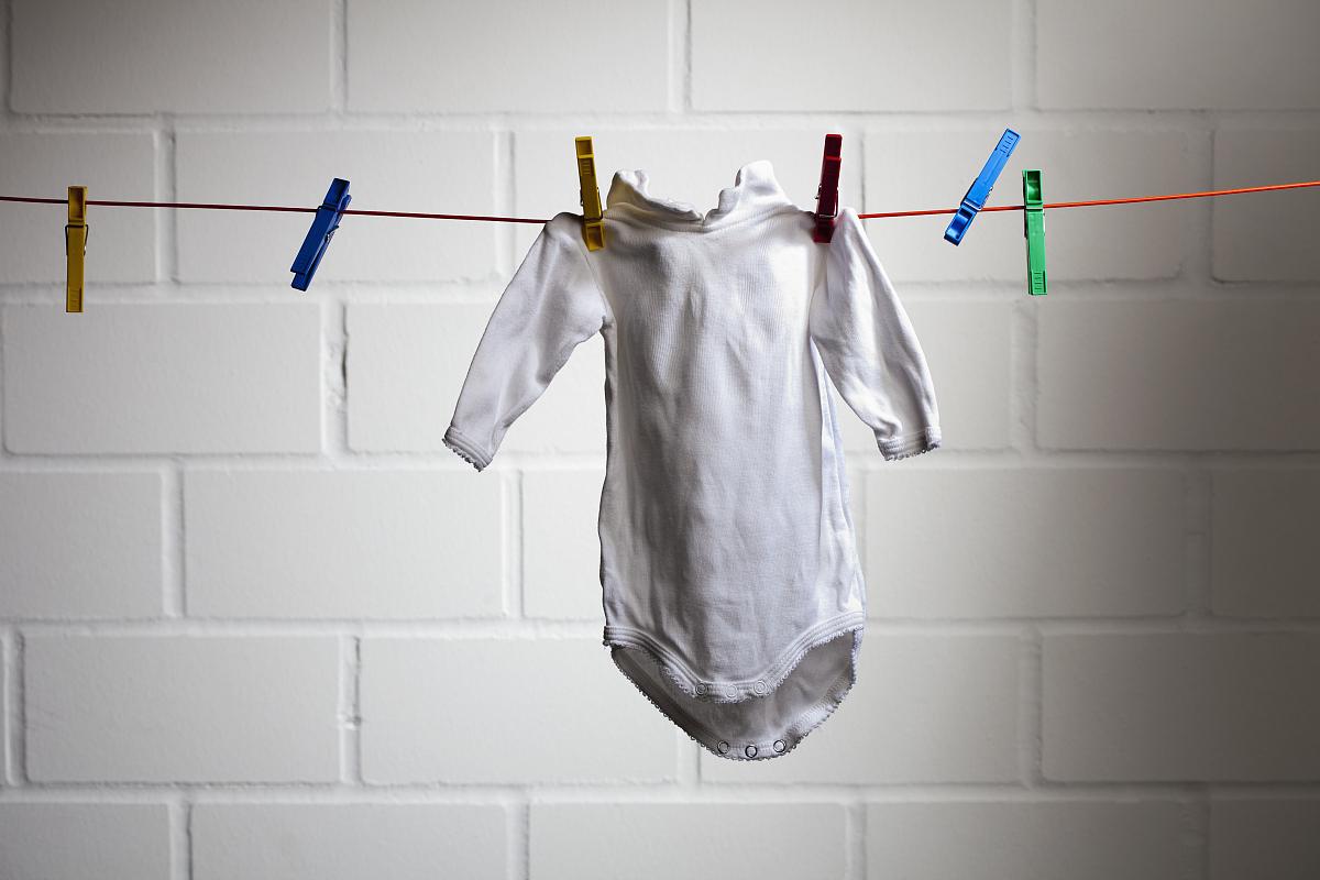 衣_从晾衣绳上挂着一个婴儿的衣服