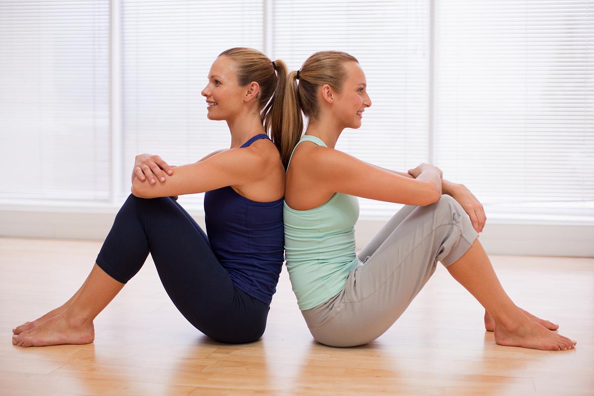 坐的_微笑的女性坐在健身室背部的肖像