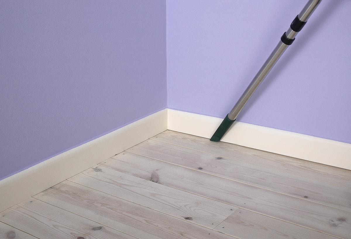 用真空吸尘器清除之间延伸踢脚线和地板的灰尘图片