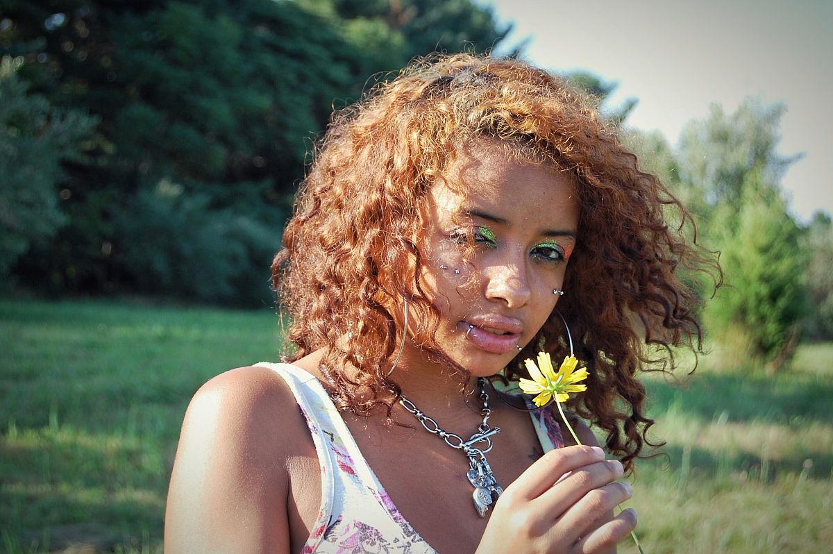 美丽的女人手捧鲜花站在田野上图片