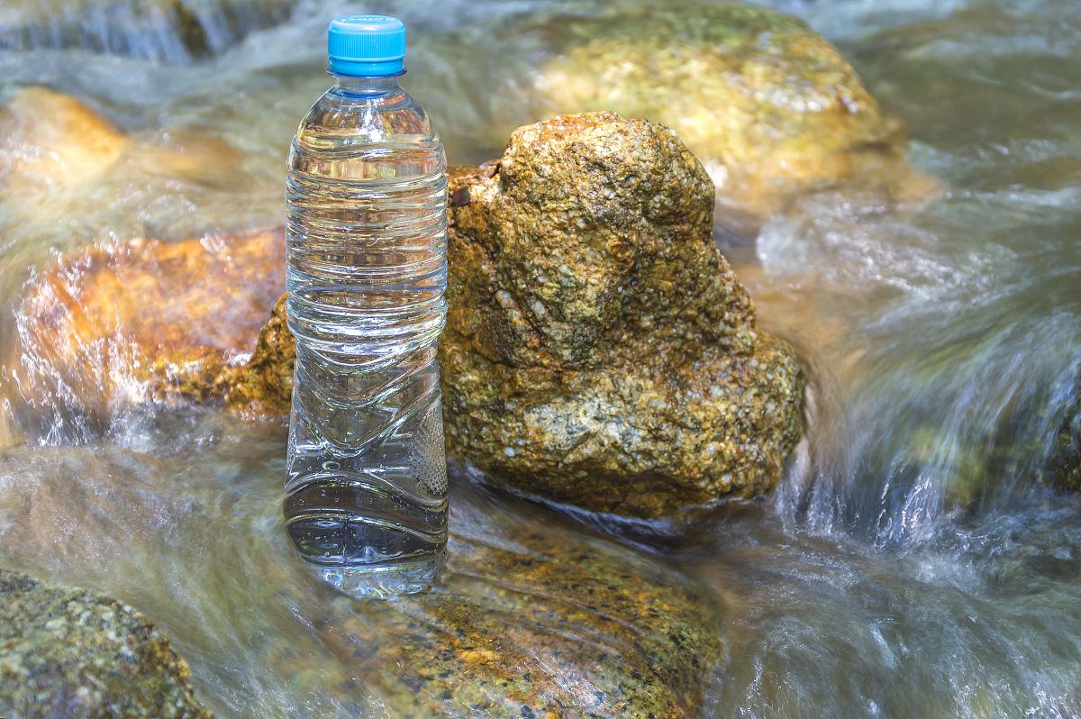 林中水流中的矿泉水瓶图片