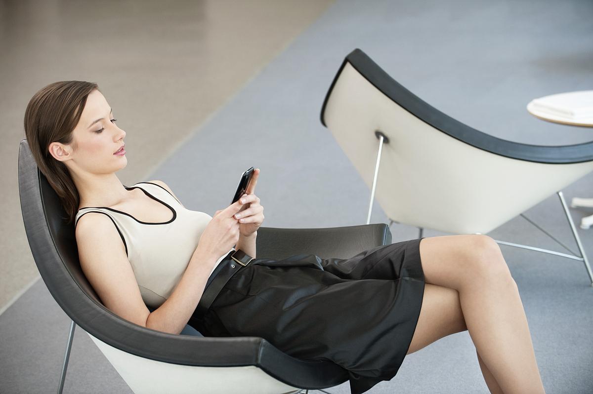 坐的_女人坐在椅子上,用手机发短信