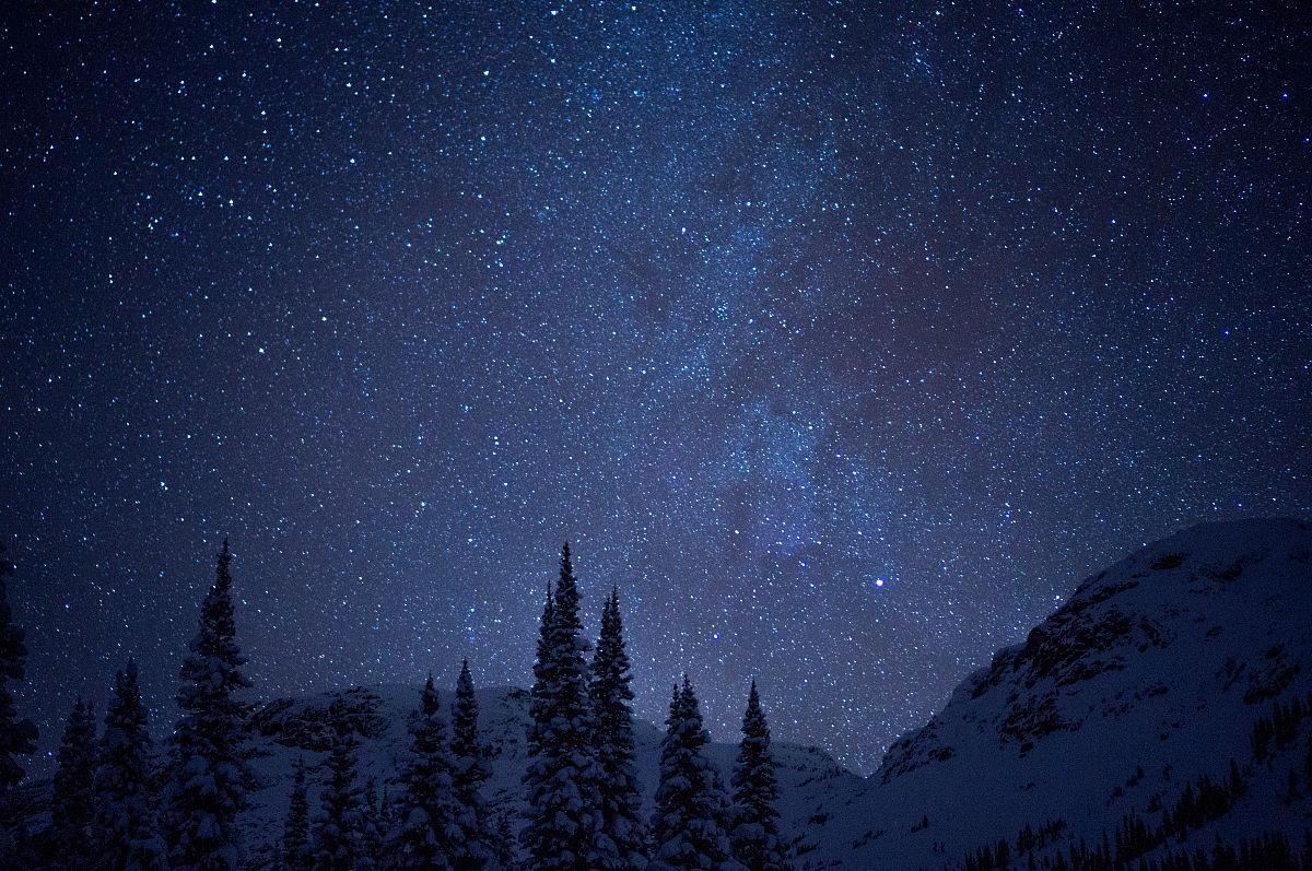 雪山覆盖星空下的树木风景图片