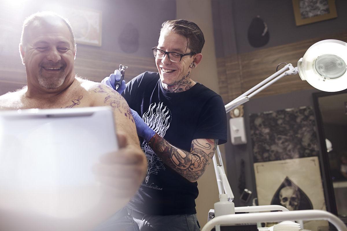 微笑的人与数字平板得到肩纹身图片