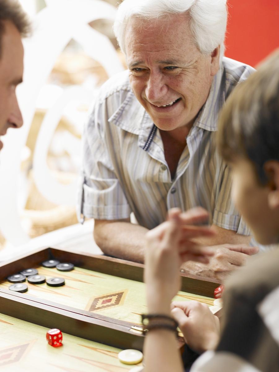 男孩(8-10)与父亲和祖父玩五子棋(差分焦点)图片