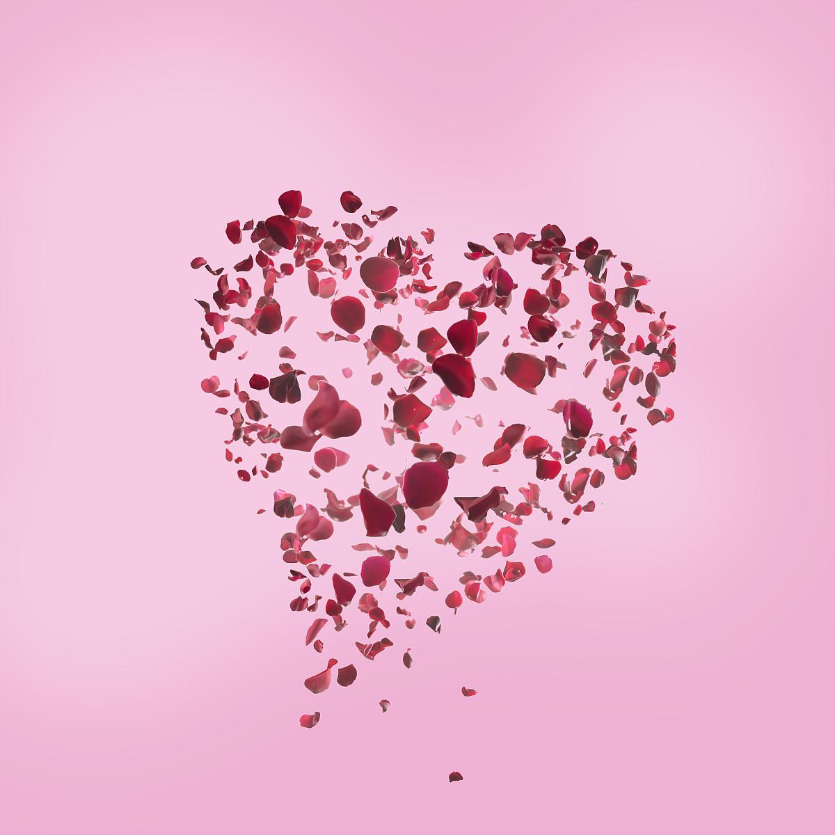 心形的玫瑰花瓣在粉红色的背景图片