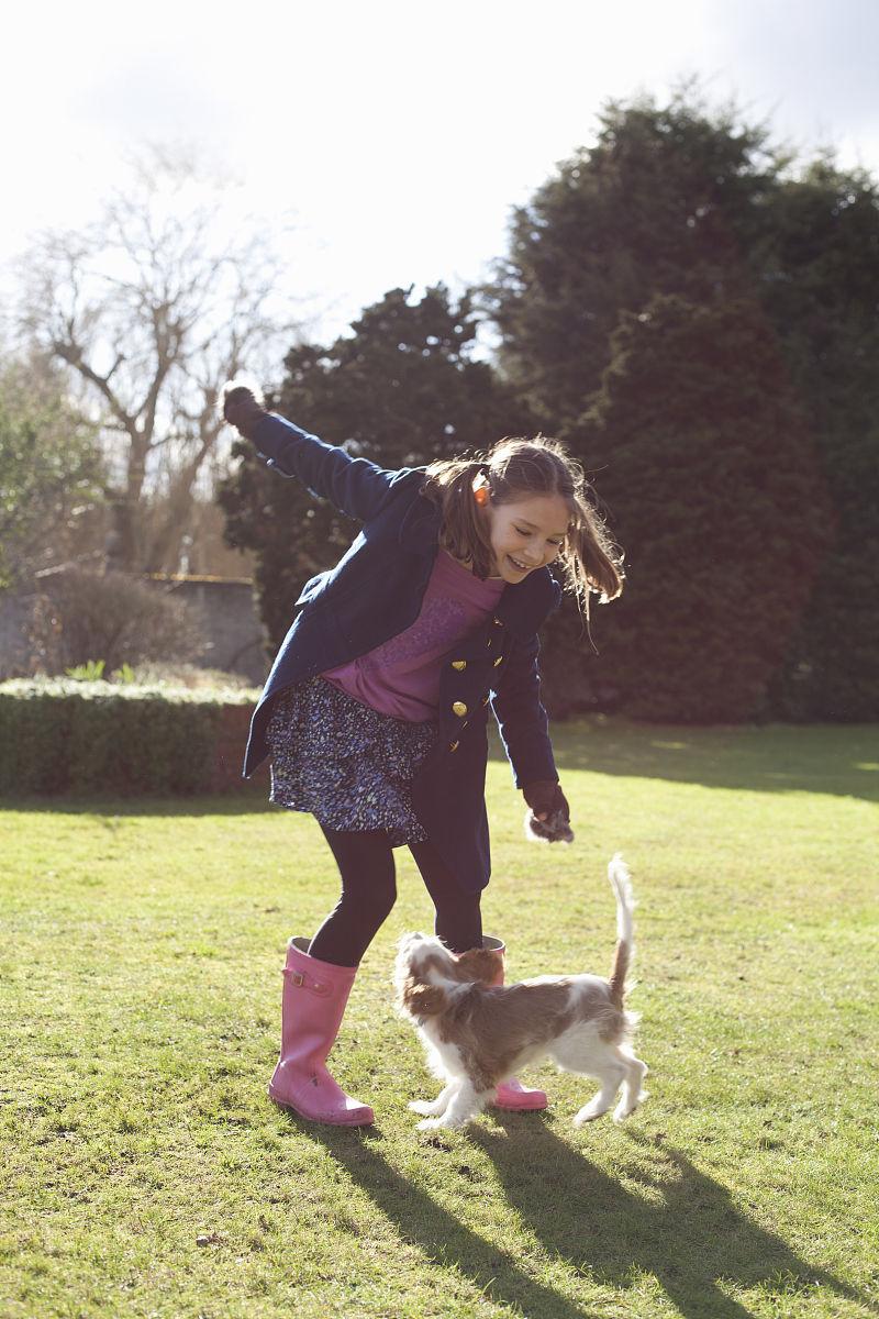 女孩在花园里和她的宠物狗玩耍图片