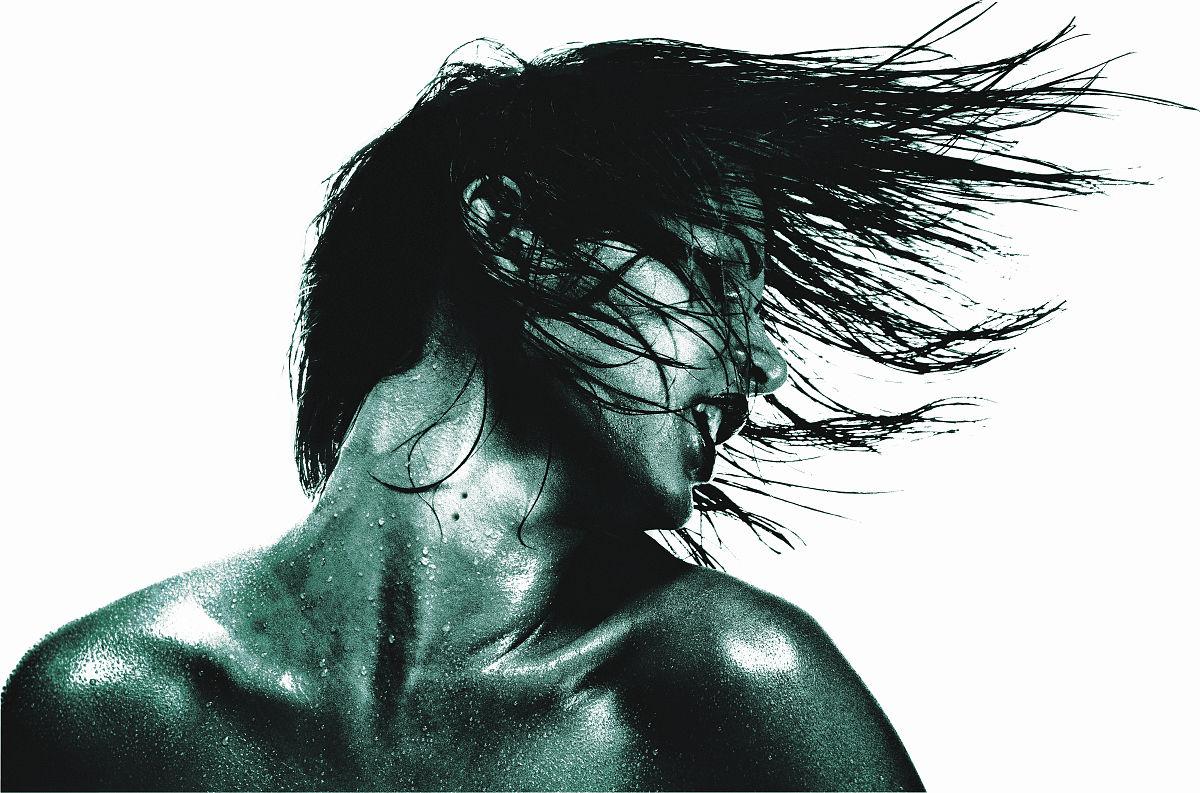 年轻的女人捋头发(色调的黑白)图片