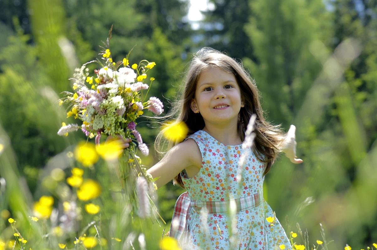 女孩(6-7)与一群鲜花在草地上,微笑,特写图片