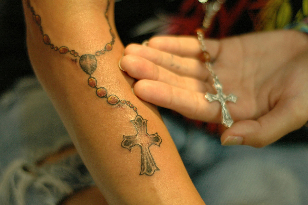 裁剪的手显示纹身和十字架图片