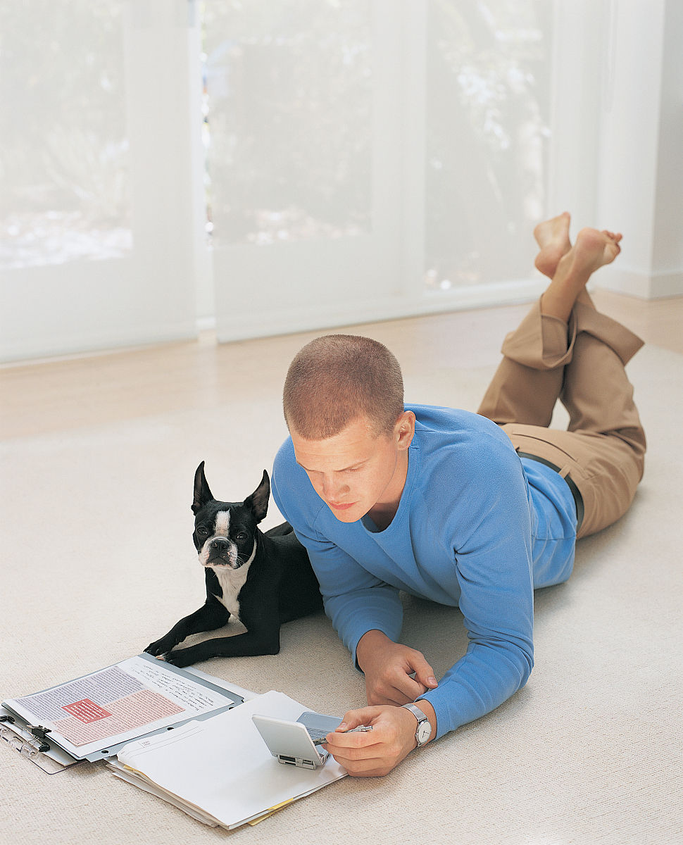年轻的商人躺在地板上,他的宠物狗和工作在家里在他的掌上电脑图片