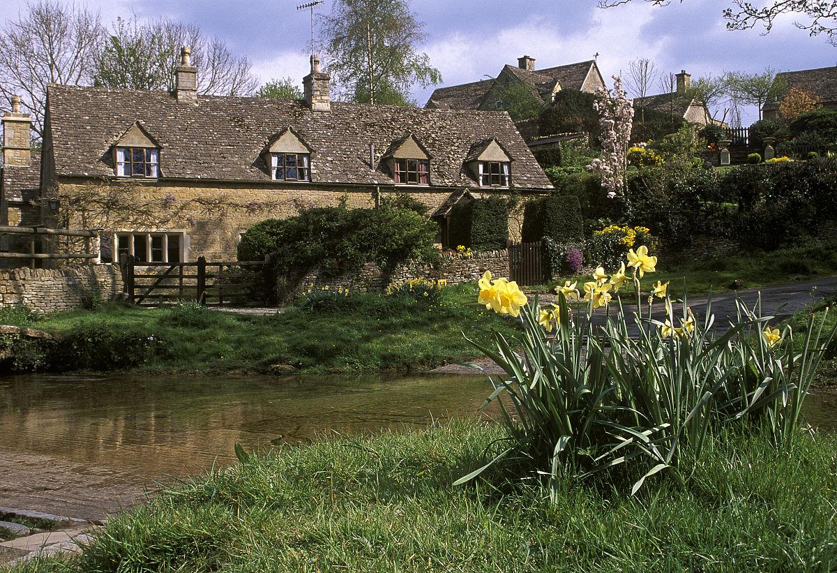 田园诗般的科茨沃尔德石头小屋旁边的福特与河岸上的水仙图片