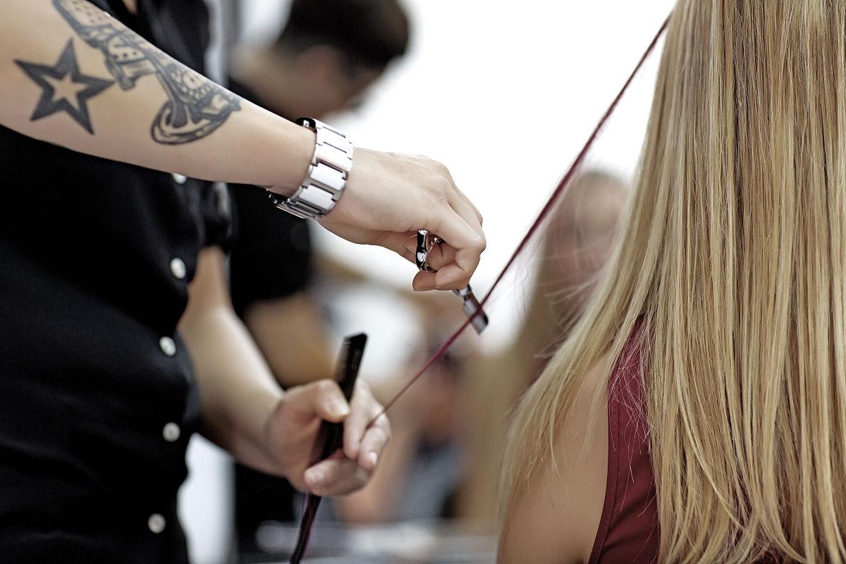 纹身女发型师工作的金发女人客户端图片