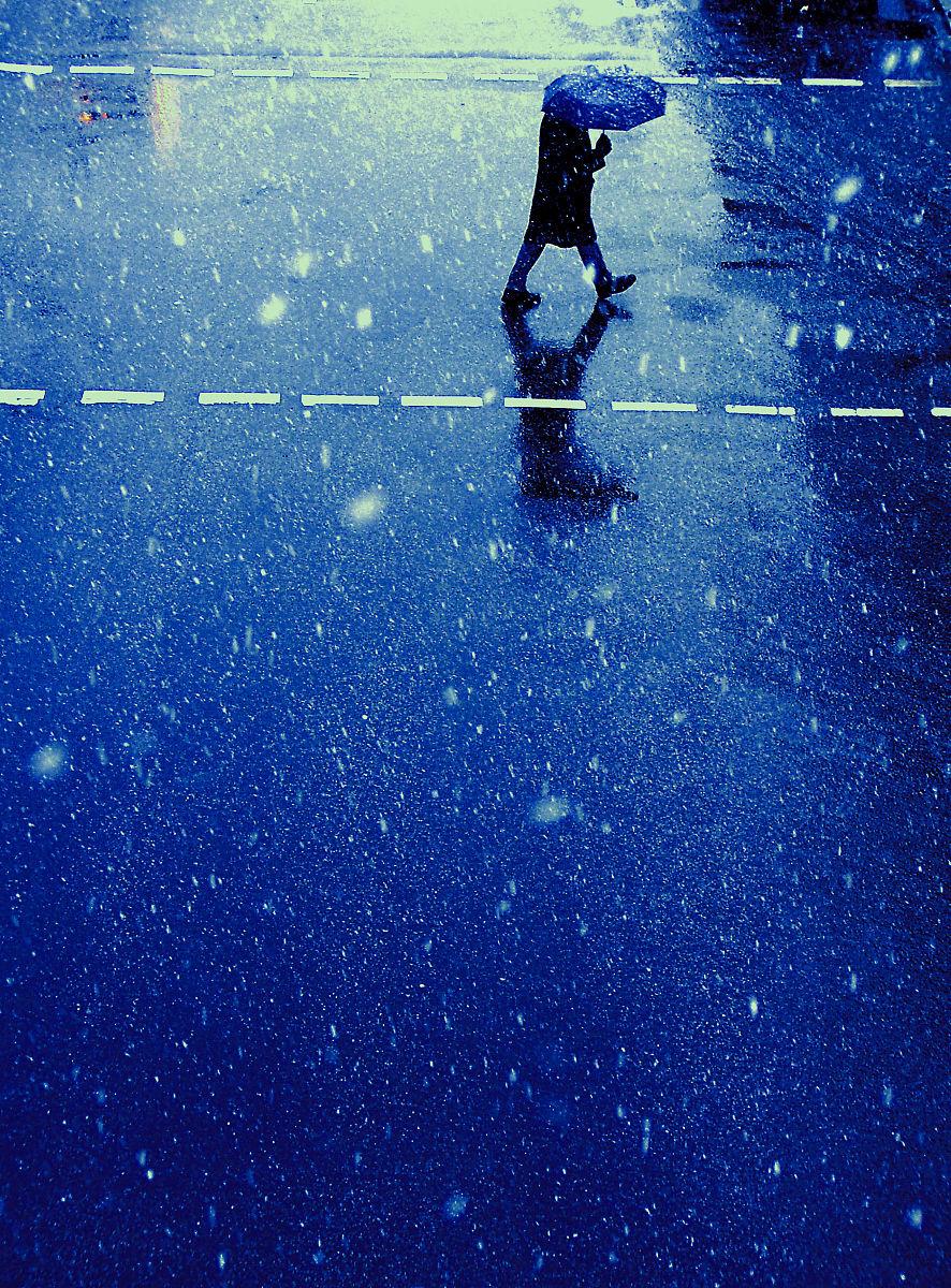 下雨天带着雨伞走过街道的男人