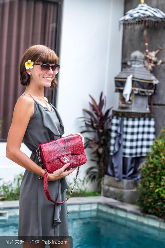 时尚的女人抱着豪华时尚的蛇皮的python包.优雅的服装.