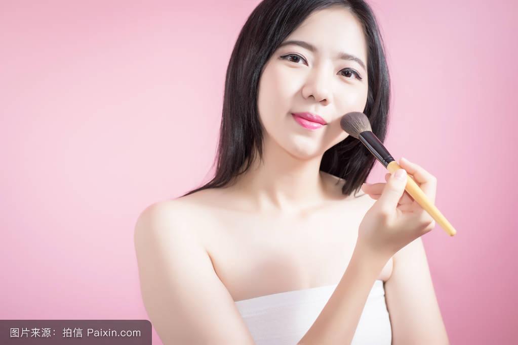 长发亚洲年轻美女用化妆粉刷在光滑的脸上隔离粉红色背景.图片